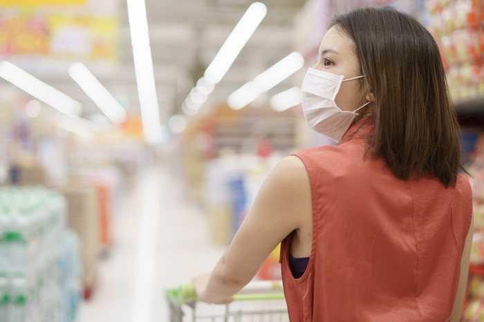 A woman in a face mask pushes a cart  down a grocery aisle.
