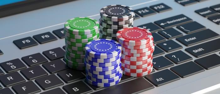 poker chips sitting on a laptop keyboard