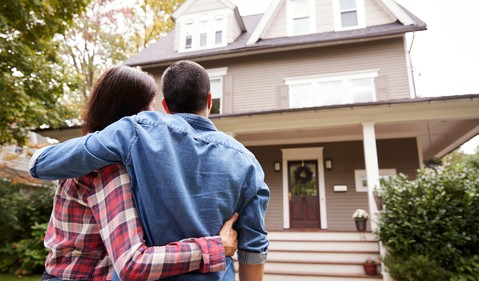 A couple embraces in the front yard while looking at their new home