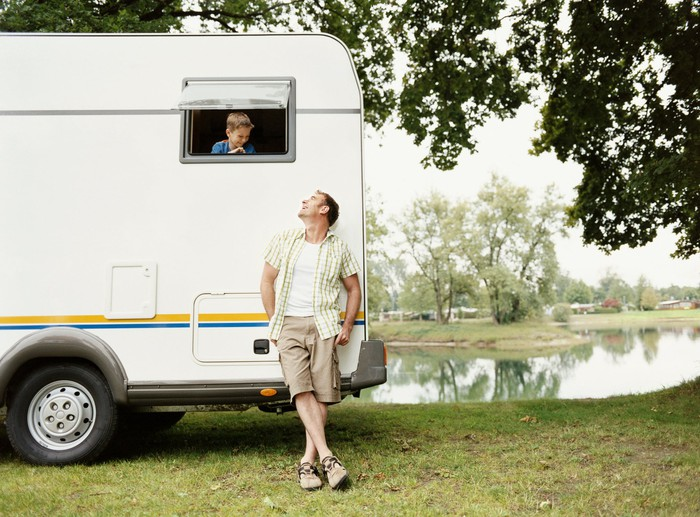 A man leaning up against an RV looking up at a little boy peering out of the RV's back window, with a pond in the background