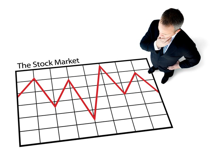 Man standing over large chart showing turbulent stock market trend.
