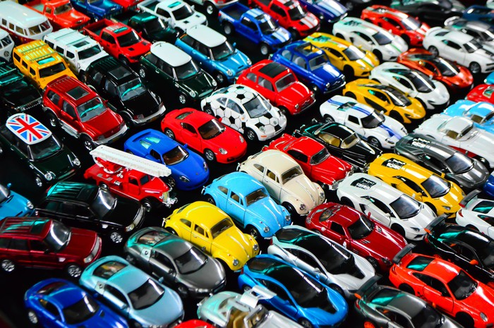 A large collection of toy cars arranged in rows.