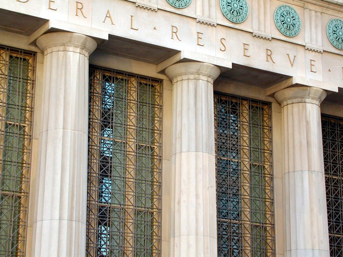 Closeup view of a Federal Reserve building with columns and blue-green ornamentation