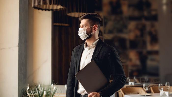 A masked restaurant server.