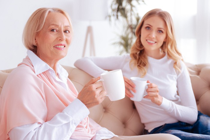 Older woman having coffee with millennial female.