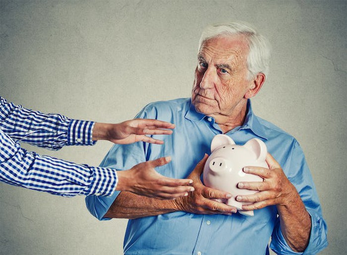 Older man holding piggy bank close to his chest, away from a pair of hands reaching to take the bank.
