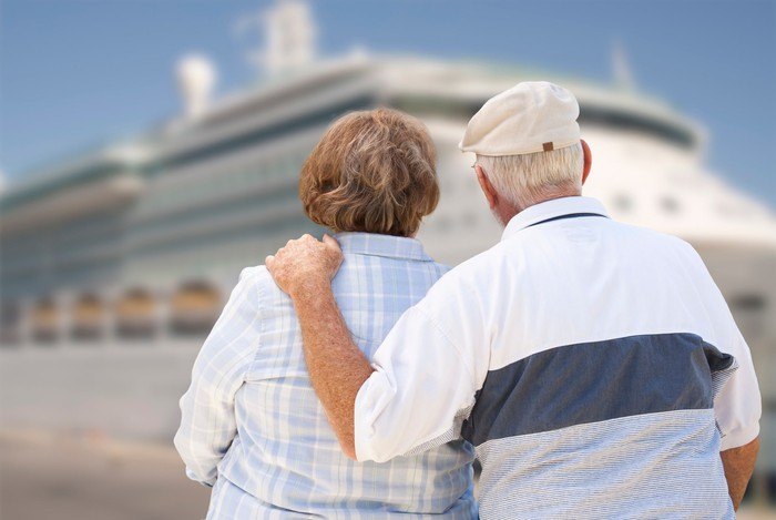 A man and woman are looking at a cruise ship.