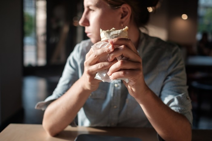 A young woman is eating a burrito.