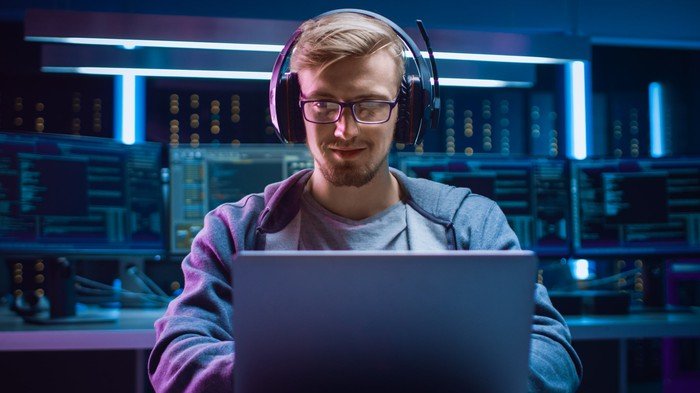 A young man uses a notebook computer while wearing headphones.