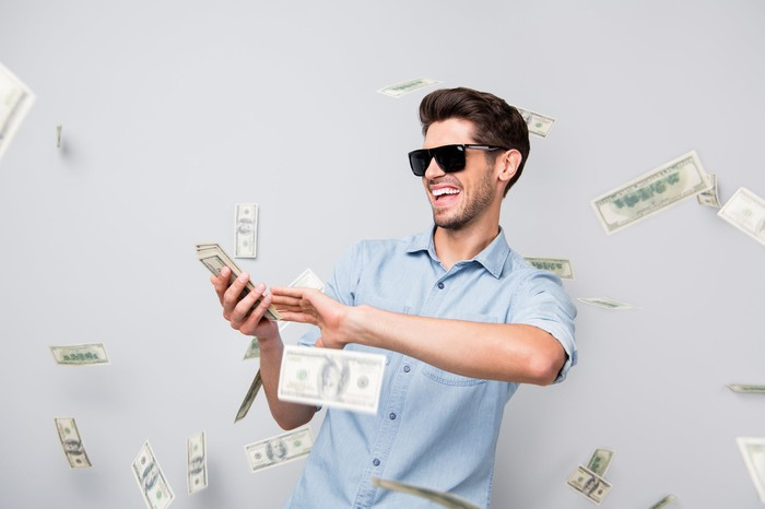 Smiling young man dealing money into the air