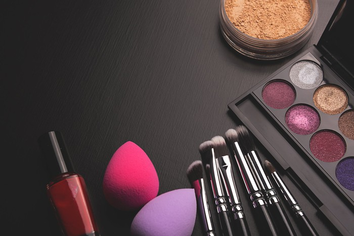 cosmetics and application brushes on a black table