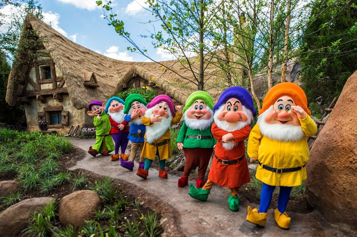 Snow White's seven dwarfs posing in front of their ride at Disney World's Magic Kingdom.