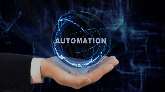 Hand holding lit blue globe that says Automation