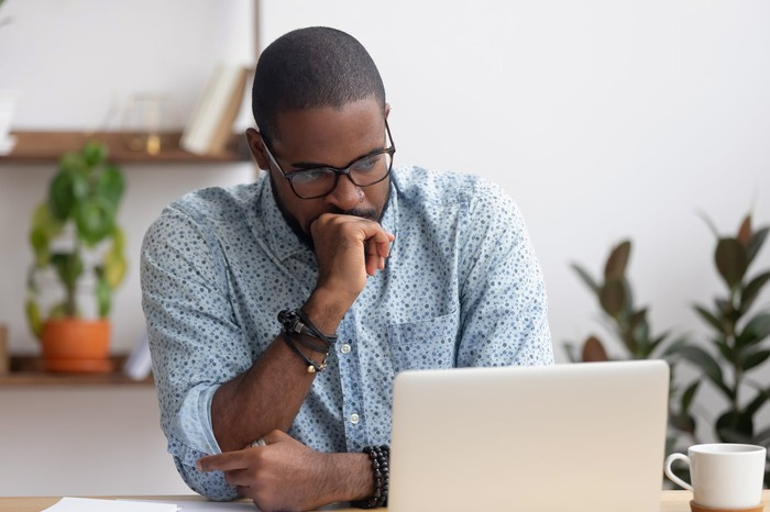 Man at laptop with serious expression resting fist on chin