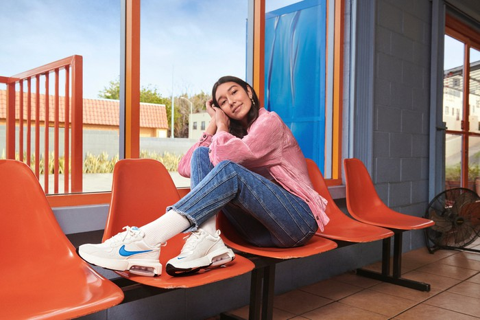 A young woman wearing Nike sneakers.