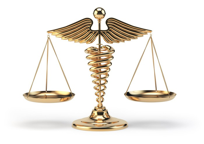 A scale in the form of the medical Caduceus symbol.