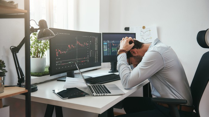Man holding his head while seated at desk with two monitors displaying graphs