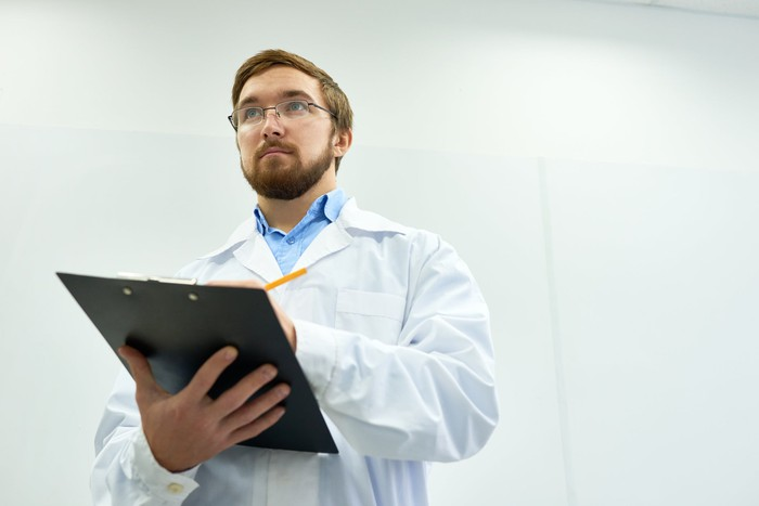 Person in a white lab coat writing on a clipboard.