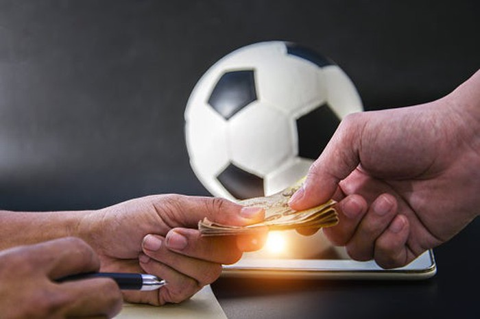Two hands exchanging money in front of soccer ball