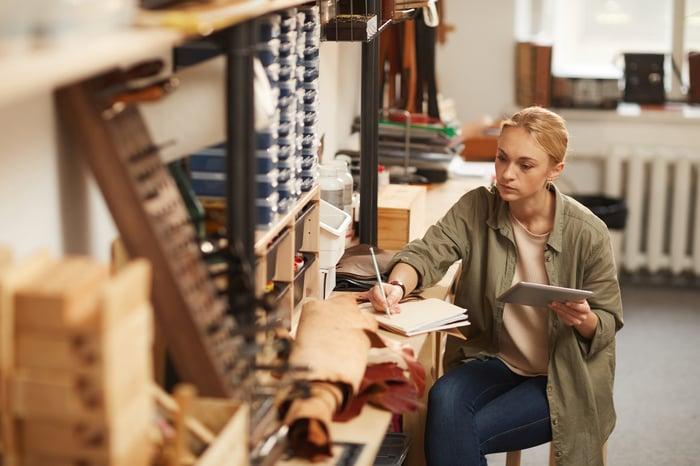 Woman in workshop writing in notebook
