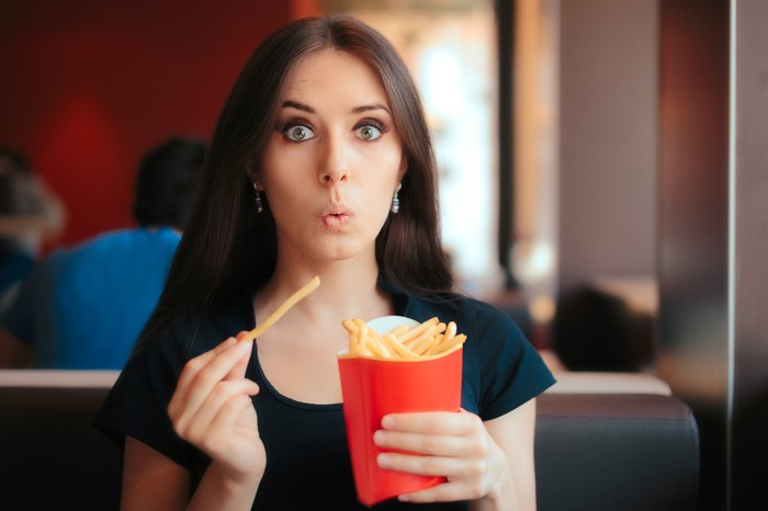 A woman digging into a box of fries.