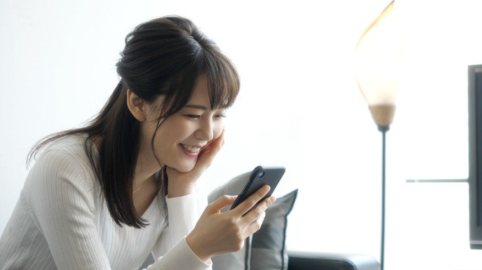 A young woman checks her smartphone at home.