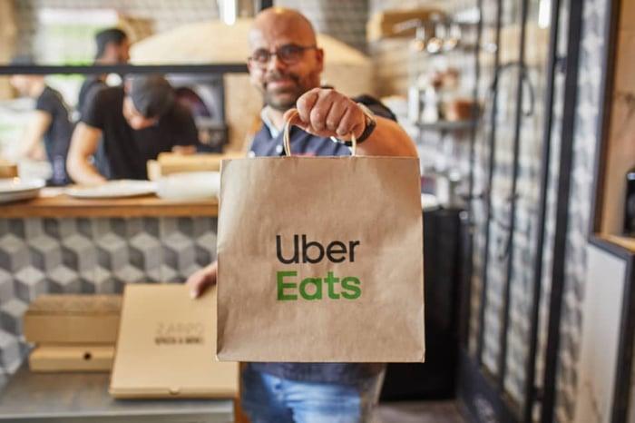 Man holding up Uber Eats bag