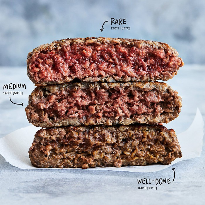 Three meat-substitute patties from Impossible Foods stacked on top of each other to show varied coloration.
