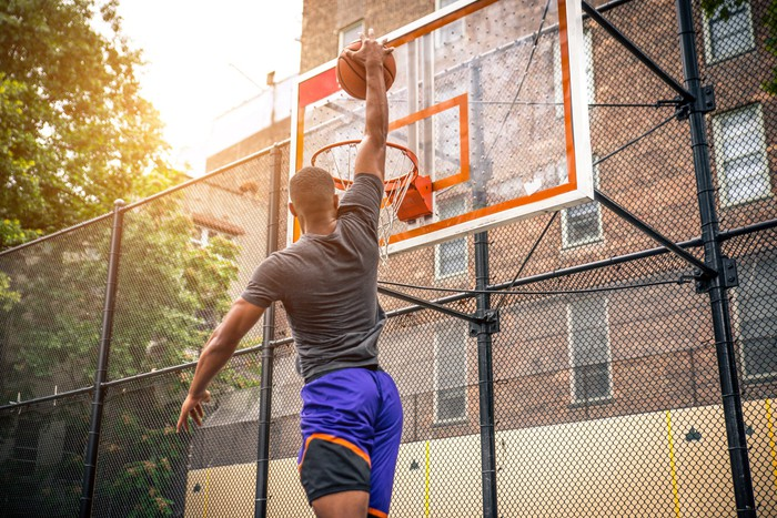 A basketball player makes a slam dunk at an outdoor court.