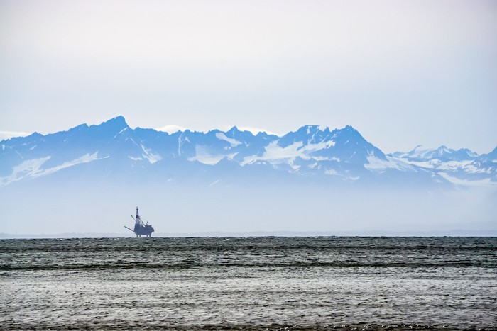 An oil platform in the icy waters off Alaska with snow-capped mountains in the background.