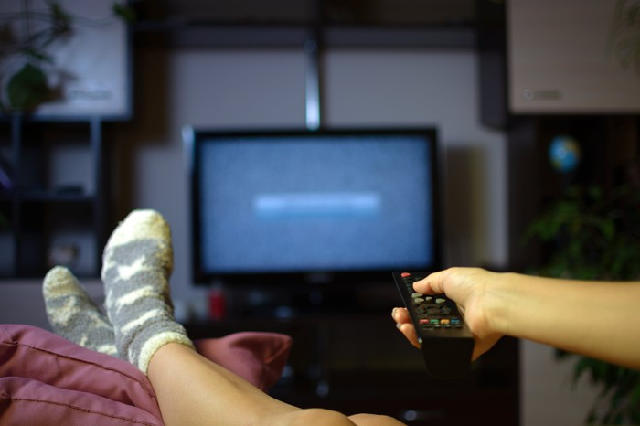 Consumer with feet propped up watching television with a remote in hand.