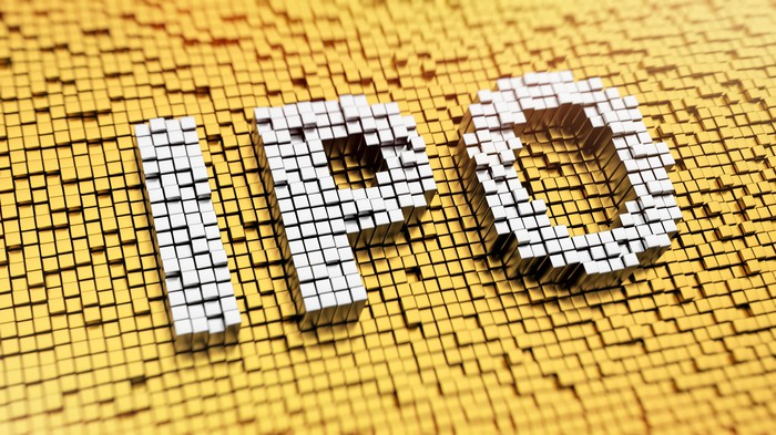 White mosaic tiles spelling IPO on a background of yellow mosaic tiles.