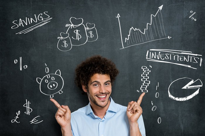 A young man is smiling in front of a blackboard with financial images on it.