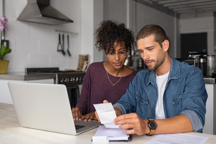 A man and woman sit in front of a computer, looking over a paper document together.