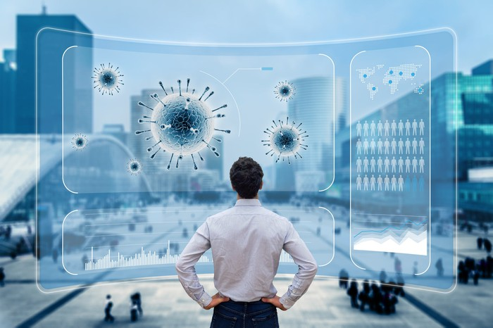 Man looking at computer images of viruses with a city in the background