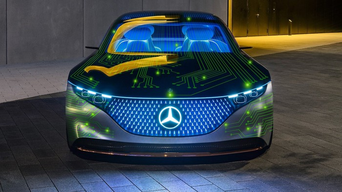 A Mercedes-Benz car covered with bright green computer circuit lines.