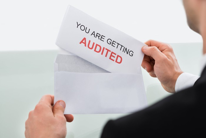 Man holding envelope with paper sticking out reading you are getting audited