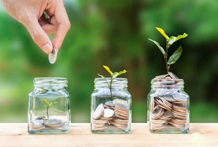 A hand places coins in glass jars with small plants growing out of them.