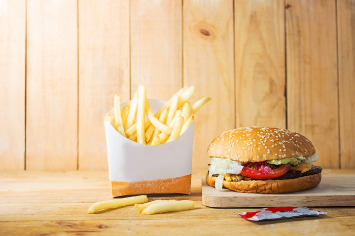 A hamburger and french fries sit on a table against a wood panel background.