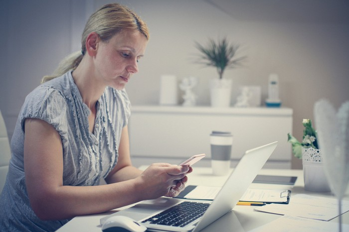 Worried woman looking at her phone in home office.