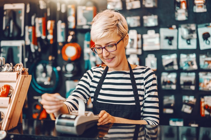 Woman in apron at store counter reaching for receipt being printed