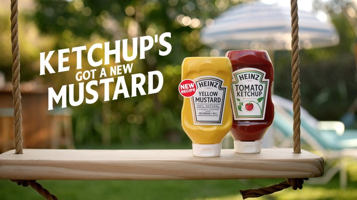 A Heinz ketchup and mustard bottle next to each other on a swing