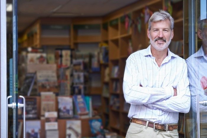 Smiling man with arms crossed standing in doorway of bookstore