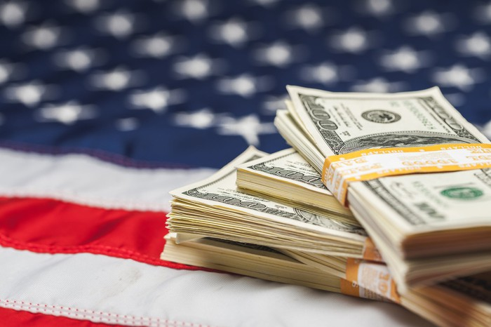 Four bundled stacks of cash lying atop an American flag.