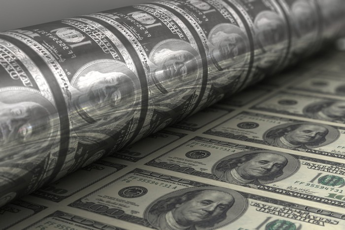A printing press producing fresh one hundred dollar bills.