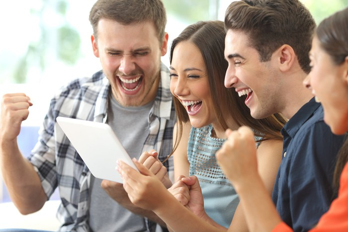 A group of young adults looks happy watching something on an iPad.
