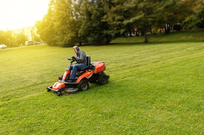 Man on lawn mower in the middle of a field