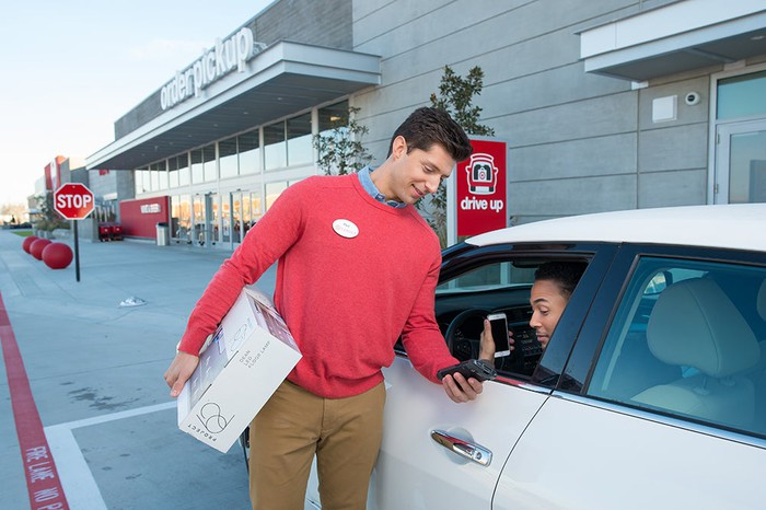 A man in a Target shirt talking to a woman while she sits in her car.