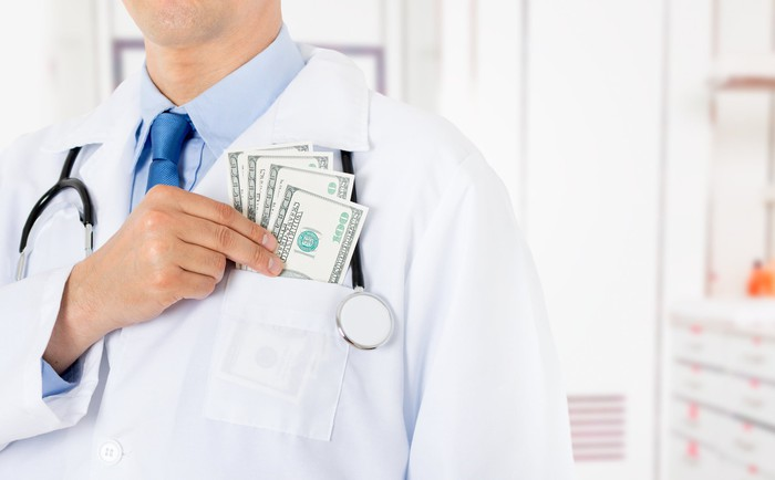 Male doctor putting $100 bills in his coat's front pocket