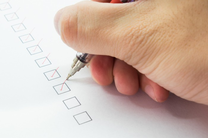 Person checking boxes off of list